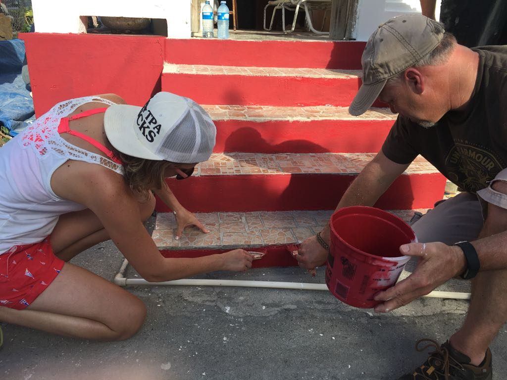 Incentive charter volunteers painting the steps of houses damaged by hurricane Irma